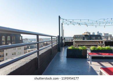 DENVER, COLORADO - SEPTEMBER 17, 2018: Rooftop deck and seating area with a gorgeous view of downtown Denver at sunset. Taken from new apartment complex in Capitol Hill.