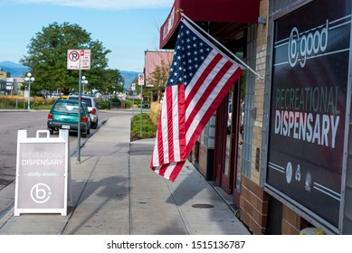 Denver, Colorado / United States of America - September 7 2019 : American flag flying outside of B Good recreational dispensary, sunny morning in front of store on sidewalk.