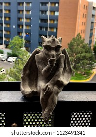 Denver, Colorado / United States - June 28, 2018:  Cast stone baby goyle thumb sucker sitting on railing of apartment balcony