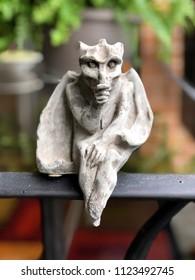 Denver, Colorado / United States - June 28, 2018:  Portrait of a thumb sucking gargoyle sitting on apartment balcony