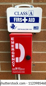 Denver, Colorado / United States - June 28. 2018:  Emergency phone and Class A First Aid Kit mounted at apartment swimming pool