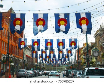 DENVER, COLORADO, USA - APRIL 8, 2017: Traffic in downtown Denver with cars and hanging state flags