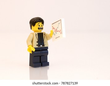 Denver, Colorado, USA - January 5, 2018: Studio shot of Lego minifigure businessman staring at a stock chart with scared look on his face.