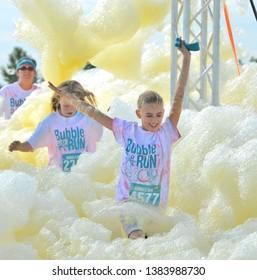 Denver, Colorado, USA. July 12, 2014. 5K Bubble Run in Denver is a special event fund raiser. Unidentified participants enjoying the bubbles.