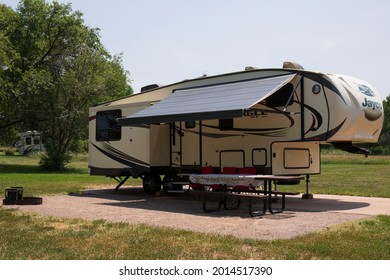 Denver, Colorado, USA - July 22, 2021.  A fifth wheel camper at Cherry Creek State Park in Denver.  Green trees and grass with pale sky.  5th wheel on pad with awning extended.