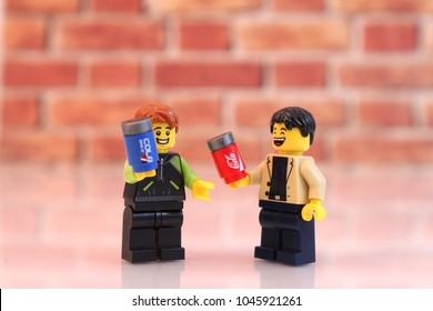 Denver, Colorado, USA - March 9, 2018: Studio shot of Lego minifigure men holding cola cans with brick background.