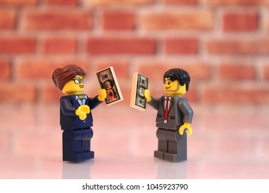 Denver, Colorado, USA - March 9, 2018: Studio shot of Lego minifigure businessman and business woman holding money.