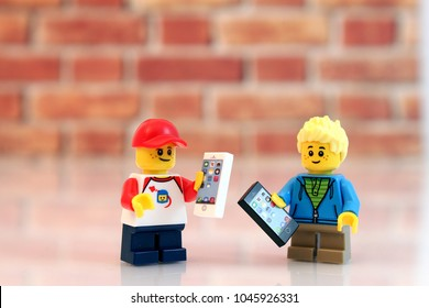 Denver, Colorado, USA - March 9, 2018: Studio shot of Lego minifigure boys holding cell phones with brick background.