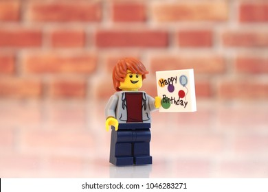 Denver, Colorado, USA - March 9, 2018: Studio shot of Lego minifigure boys holding Happy Birthday signs with brick background.