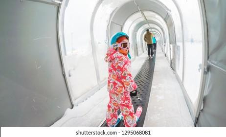 Denver, Colorado, USA-December 1, 2018 - Little girl riding up magic carpet on learning ski hill.