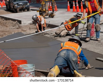 Denver, Colorado-April 9, 2011: Road construction worker on new concrete road in downtown Denver, Colorado.
