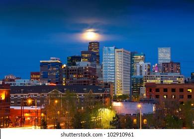 Denver skyline at dusk with the full moon rising above