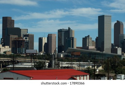 Denver Skyline with Red Roof in the Foreground seat against a blue sky background.