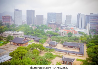Deoksugung Palace, historic center of Seoul, downtown. Around the tall buildings. Far away mountains, cloudy sky.