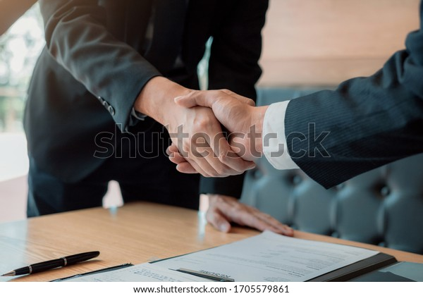 Department heads manager are shaking hands and accept to new employee in office room.