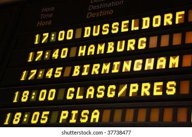 Departure board at an airport in Spain. Flights to Dusseldorf, Hamburg, Birmingham, Glasgow and Pisa.