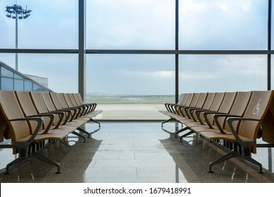 Departure lounge at the airport with seats in a row and blue sky behind the windows.