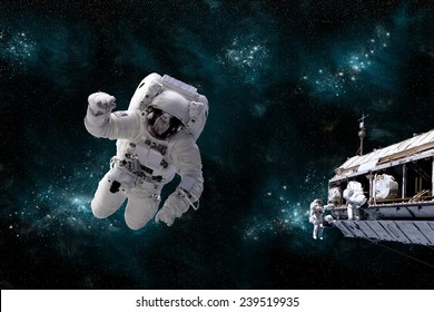 A depiction of an astronaut floating in outer space while his fellow astronauts work on the space station.  A galactic scene serves as background. Elements of this Image Furnished by NASA.