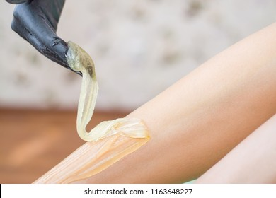 depilation and beauty concept - procedure of hair removing on leg beautiful woman with sugar paste or wax honey and black gloves hand