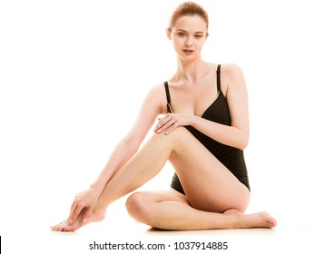 Depilation, epilation, clean, fresh skin concept. Woman in black swimsuit underwear sitting on floor, showing and touching her legs. Studio shot isolated