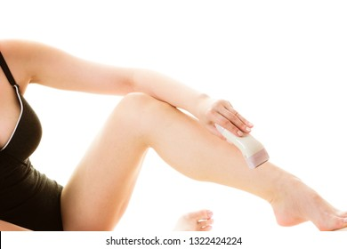 Depilation, epilation, hygiene concept. Woman shaving her legs with electric shaver depilator wearing black swimsuit, isolated.