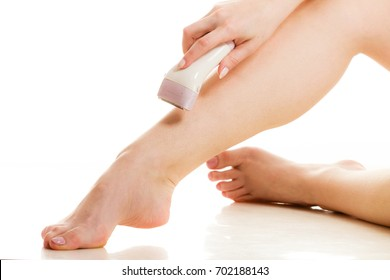 Depilation, epilation, hygiene concept. Woman shaving her legs with electric shaver depilator, isolated.