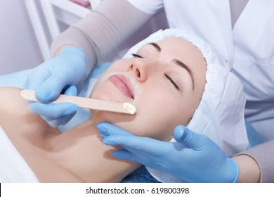 depilation with hot wax mustache in the beauty salon. Young woman receiving facial epilation closeup. Beautician removes hair on face