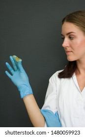 depilation master girl in blue medical gloves stretches with her fingers a drop of wax for shugaring