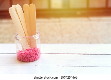 depilatory pearly pink  solid wax beans and wooden stick wood on wood background