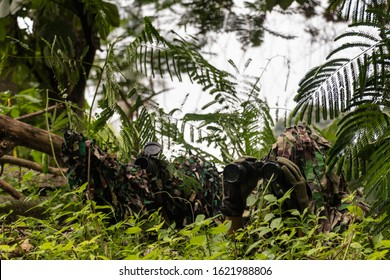 Depok, Indonesia - 23 February 2019 : Sniper and spotter in urban combat training. Full ghillie camo suit and a high power sniper rifle. In urban combat training ground. Aiming his weapon.