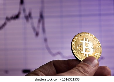 Depreciation of virtual money bitcoin. Hand with bitcoin amid declining sales schedule on the virtual exchange.
