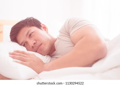 Depress man is lying late morning on bed