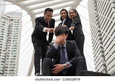 Depress sad Businessman sit on footpath of modern city while other Business coworkers laugh at him. Head down with feeling bad covered face by  hand. Failure, Fired,  unemployed from industry.