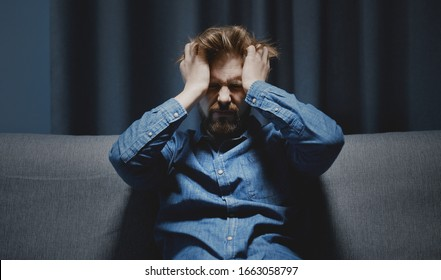 Depressed adult man in denim shirt squeezing head with both hands sitting on couch in dark room