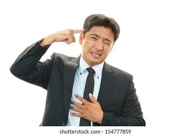 Depressed Asian businessman.
