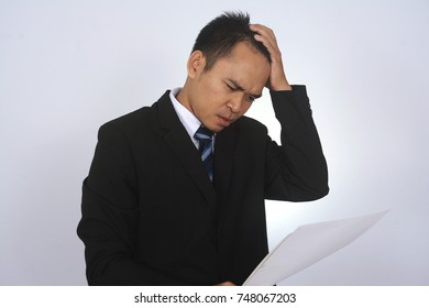 Depressed Asian Businessman holding head in hands