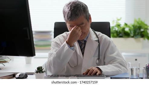 Depressed asian senior doctor feel tired and has eyes fatigue