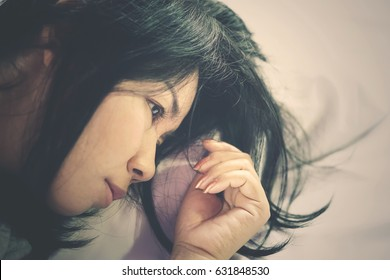 depressed Asian woman in bed having problem to sleep at night ,  insomnia woman unhappy and thinking in bed.