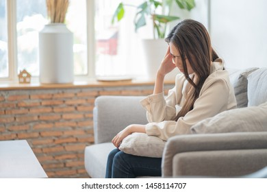 Depressed Asian woman headache and back pain sitting on sofa.panic attacks. sad fear stressful  emotional.person with health anxiety,people bad feeling down