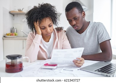 Depressed bankrupt young african american family sitting at kitchen table, feeling stressed while reading notification, informing about eviction from their appartment because housing debt. No money