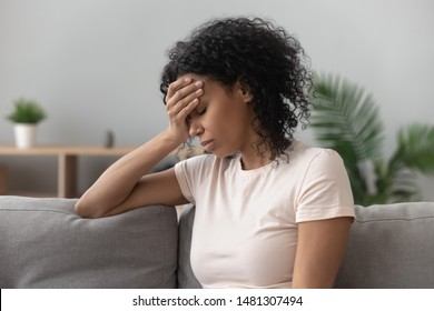 Depressed black young woman sit on sofa down upset having personal relationships problems, stressed millennial african American girl touch head feel despair mourning or grieving of loss