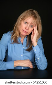 depressed blond middle aged woman on black background