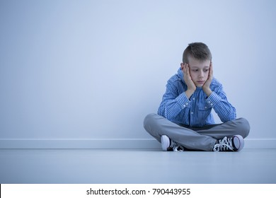 Depressed boy with Asperger syndrome sitting alone against a wall with copy space