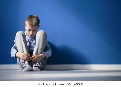 Depressed boy sitting on a floor in blue room