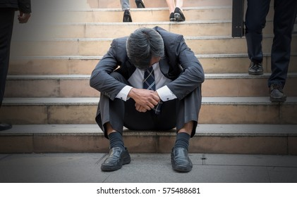 Depressed businessman bending down the head sitting on the stairs. Unemployed Middle edge man feel frustrated after business failure.