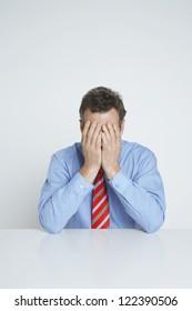 Depressed businessman covering eyes while sitting at desk