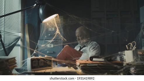 Depressive Geschäftsleute, die mit Geschäftsausfällen zu tun haben: er sitzt in seinem verlassenen Büro und sucht nach Papierkram