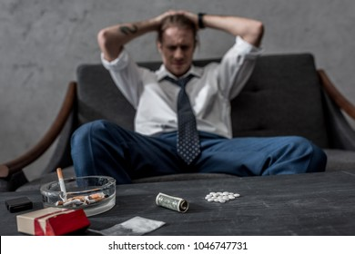 depressed businessman with drug addiction sitting on couch in front of table with mdma pills