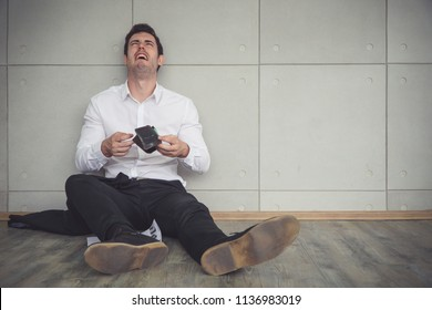 Depressed businessman holding the empty wallet and crying. Termination and unemployment concept.