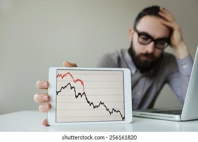 Depressed businessman leaning head below bad stock market chart in office
